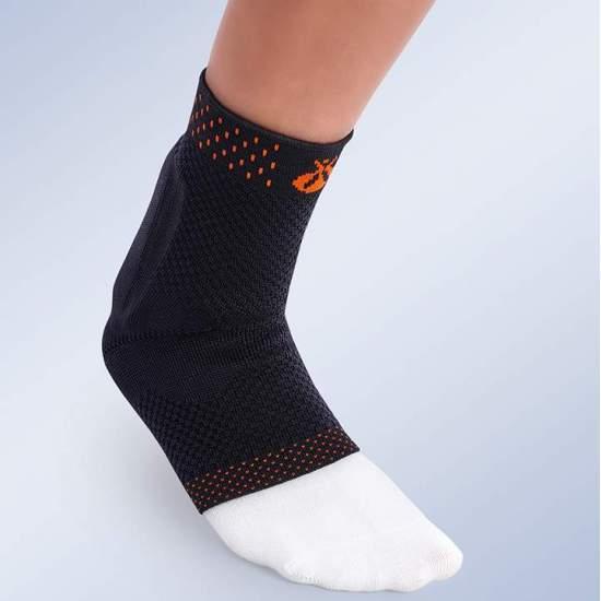 Cheville élastique avec coussinet pour tendon d'Achille et appui auriculaire Orliman 9402 - Fabriqué en tissu élastique respirant grâce à un tricot plat et à un design anatomique. La partie inférieure du talon est profilé, ce qui le rend plus confortable et imperceptible.